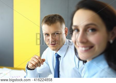 Man And Woman Colleagues Are Sitting At Table In Office