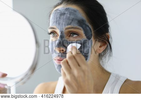 Woman Washing Off Black Clay Mask From Her Face