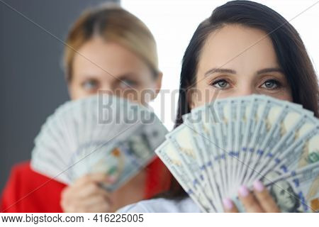 Two Young Women Holding Dollars In Front Of Their Face