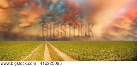 Green field with a road and a beautiful stormy sky. Summer panorama