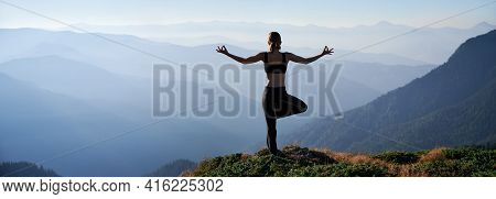 Silhouette Of Young Woman Performing Yoga Pose On Grassy Hill And Looking At Beautiful Mountains. Sp