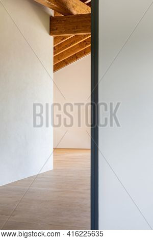 Detail of an open door, empty white room with exposed wood beams and hardwood floors. No one inside.