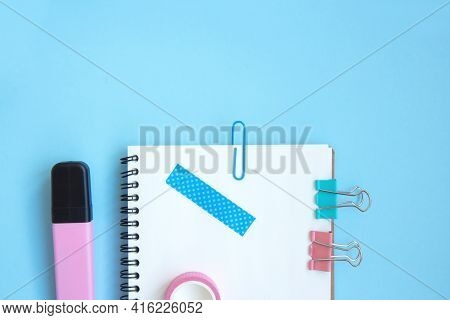 White Open Notebook With Paper Clip, Clip And Piece Of Scotch Tape On Blue Background. Set Stationer