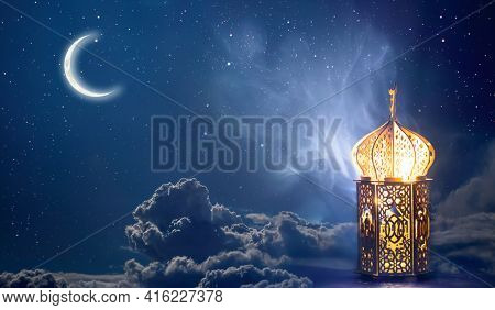 Ornamental Arabic lantern with crescent moon glowing at night. Festive greeting card for Muslim holy month Ramadan Kareem.