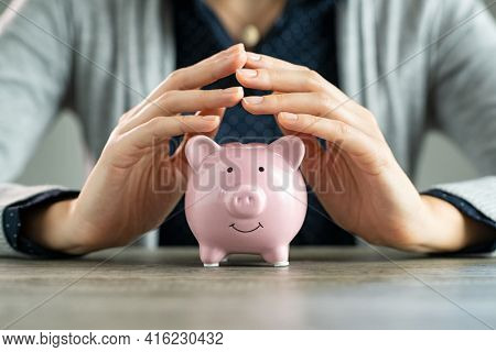 Close up of hands of woman protecting piggy bank for saving. Hands covering savings on table. Closeup of pink piggy bank protected by woman hands. Save money, investment and financial safety concept.
