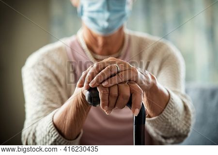 Close up of senior disabled woman hands holding walking stick and wearing face protective mask during covid19 pandemic. Detail of old woman hands holding handle of walking cane during covid pandemic.