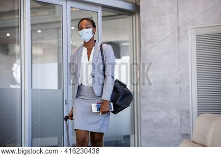 African american business woman walking with surgical mask during covid-19 pandemic in airport. Happy mature black woman walking at terminal with luggage and passport wearing protective face mask.