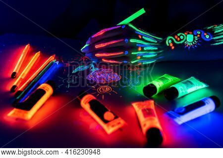 Hand With Fluorescent Glowing Pattern Holding Neon Pencil. Fluorescent Paints And Pencils Are On The