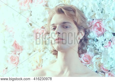 Handsome young man with blond wavy hair and athletic body poses on a background of roses. Perfumery and beauty products. Men's beauty.
