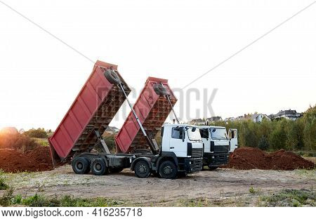 Two Red Dump Trucks Simultaneously Lifted The Bodies To Unload The Sand. Cargo Transportation Servic