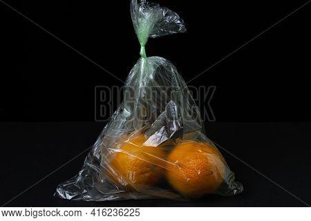 Oranges In A Plastic Bag On A Black Background. Oranges On A Dark Background. Buying Oranges