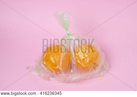 Oranges In A Plastic Bag On A Pink Background. Oranges On A Light Background. Buying Oranges