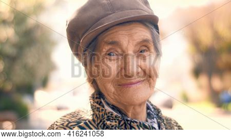 Portrait of happy smiling 92 year old senior woman outdoors. Closeup, shallow DOF.