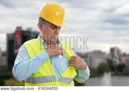 Old Male Constructor Wearing Hardhat And Work Equipment Hiding Cash Money Salary In Chest Pocket Of