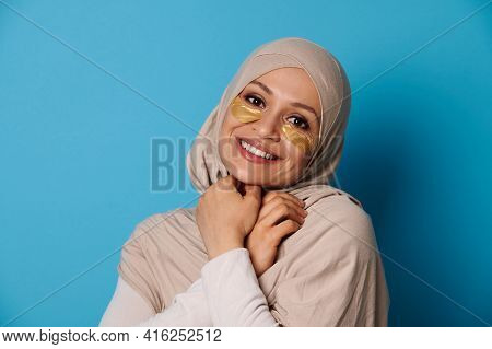 Beautiful Woman With Covered Head In Hijab, Smiling At Camera With Hydrogel Collagen Patches Under E