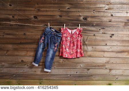 Children's Fashion Set Of Girls Clothing, Blouse And Jeans; Photo On Wooden Background.