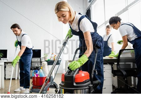 Cleaner In Overalls Using Vacuum Cleaner Near Multiethnic Colleagues In Office.