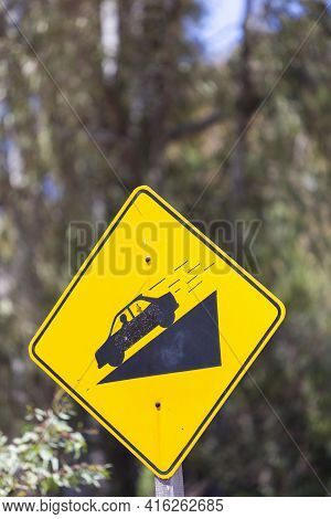 Yellow Vintage Warning Steep Road Sign Slope And Car On Hill,  Blurred Background. Argentina
