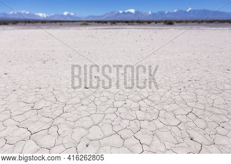 Drought Land On The Pampa Of El Leoncito With The Andean Mountains Against A Clear Blue Sky. San Jua