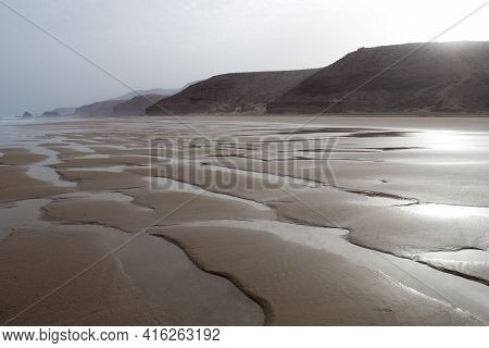 Landscape Of Empty Beach Early In The Morning With Large Cliffs, Morocco.