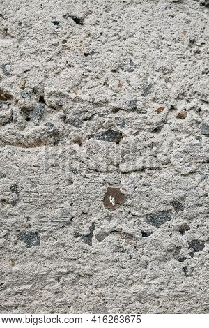 Gray Old Concrete Surface With Cracks And Stones As A Background Texture.