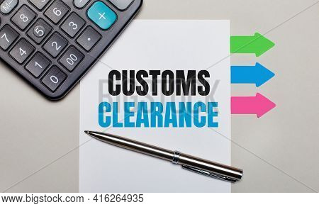 On A Light Gray Background, A Calculator, A White Sheet With The Text Customs Clearance, A Pen And B