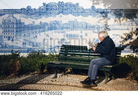 Lisbon, Portugal - February 2, 2019: Old Man Reading A Newspaper Sitting On A Bench Next To Azulejos