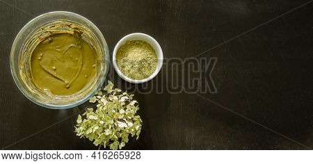 The Glass Bowl With Rehydrated Henna, Dry Henna Powder And Hydrangea Flower On Black Wooden Table. H