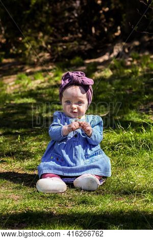 Cute baby girl outdoor in spring time on grass