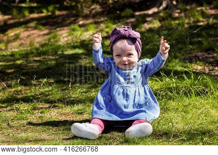 Cute baby girl outdoor in spring time on grass with hands up