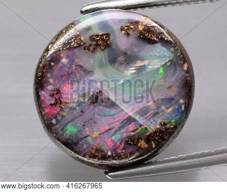 Natural Koroit Bolder Flash Opal In The Tweezers