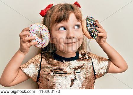 Little caucasian girl kid holding tasty colorful doughnuts smiling looking to the side and staring away thinking.