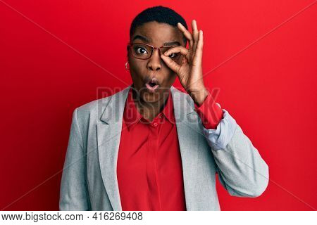 Young african american woman wearing business jacket and glasses doing ok gesture shocked with surprised face, eye looking through fingers. unbelieving expression.