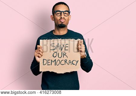 Young african american man holding save our democracy protest banner looking at the camera blowing a kiss being lovely and sexy. love expression.