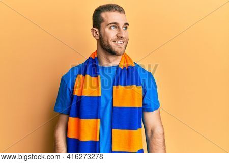 Young caucasian man football hooligan cheering game looking to side, relax profile pose with natural face and confident smile.