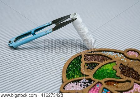 Weaving From Beads. A Box With Beads And A Skein Of Thread And Scissors. Selective Focus.