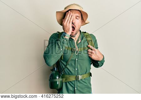Handsome man with beard wearing explorer hat and backpack yawning tired covering half face, eye and mouth with hand. face hurts in pain.