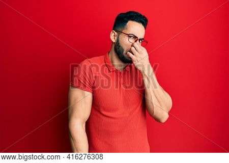 Young hispanic man wearing casual clothes and glasses smelling something stinky and disgusting, intolerable smell, holding breath with fingers on nose. bad smell