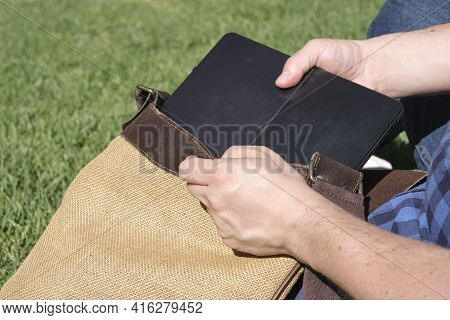Detail Of Young Hands Taking A Laptop Out Of A Rustic Bag In A Park A Sunny Day. Concept Of Digital