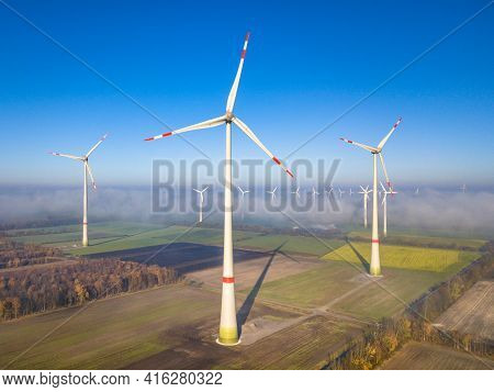 Aerial View Of Wind Turbines In Windfarm Above Mist Layer On German Countryside In The Morning Sun.