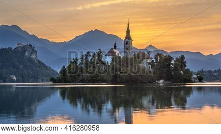 Landmark Lake Bled With St Mary's Church And Mountains In Backdrop Under Orange Morning Sky, Sloveni