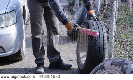 A Partially Visible Man Manually Brushes A Car Wheel Tire Before Replacing Winter Tires With Summer