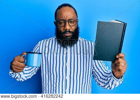 Young african american man reading book and drinking a cup of coffee skeptic and nervous, frowning upset because of problem. negative person.