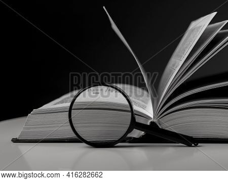 Open Book Close Up With Turning Pages And Magnifying Glass. Textbook In Hardcover On Desk. Education