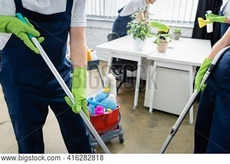 Cropped View Of Cleaners In Overalls Holding Mop And Vacuum Cleaner Near Cart With Detergents In Off