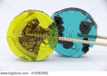Lollipop With Black Currant Inside Turquoise Color And Lollipop With Yellow Lemon Slice On A White B