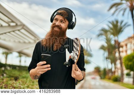 Young irish skater man using smartphone and headphones at the city.