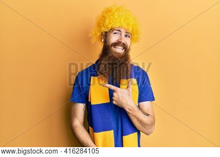 Redhead man with long beard football hooligan cheering game wearing funny wig cheerful with a smile of face pointing with hand and finger up to the side with happy and natural expression on face
