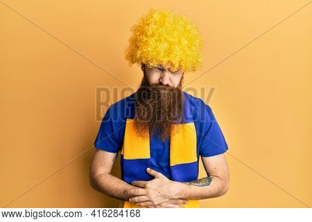 Redhead man with long beard football hooligan cheering game wearing funny wig with hand on stomach because indigestion, painful illness feeling unwell. ache concept.
