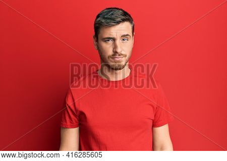 Handsome caucasian man wearing casual red tshirt skeptic and nervous, frowning upset because of problem. negative person.